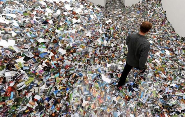 Een bezoeker waadt door 350.000 afgedrukte foto's gedownload van Flickr. Een project van Erik Kessels. Foto (c) Carsten Rehder/Getty Images